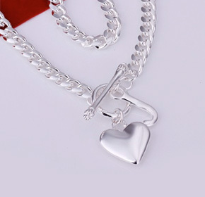 $25.00 for a Silver Heart and Fish Bone Charm Necklace  from Allure Couture Jewelry ($149.00 Value)